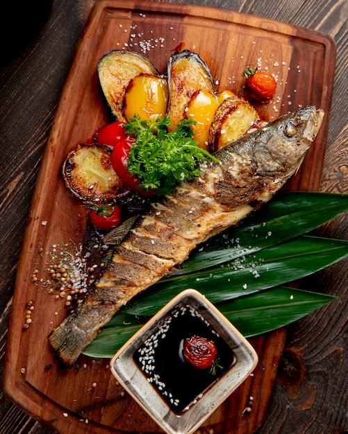 Pesce fritto con i pomodori e la salsa dei peperoni dolci delle melanzane arrostite Foto Gratuite