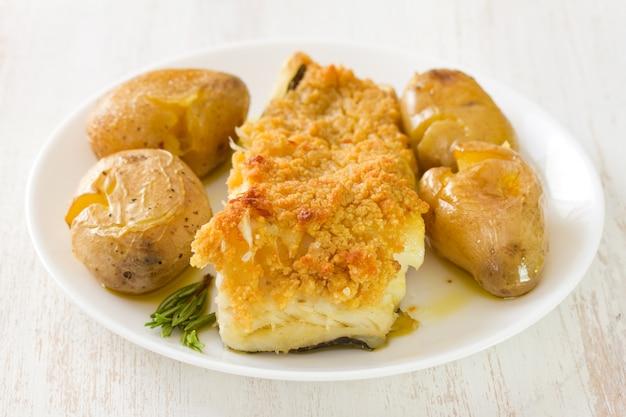 Pesce fritto con la patata e l'olio sul piatto su bianco Foto Premium