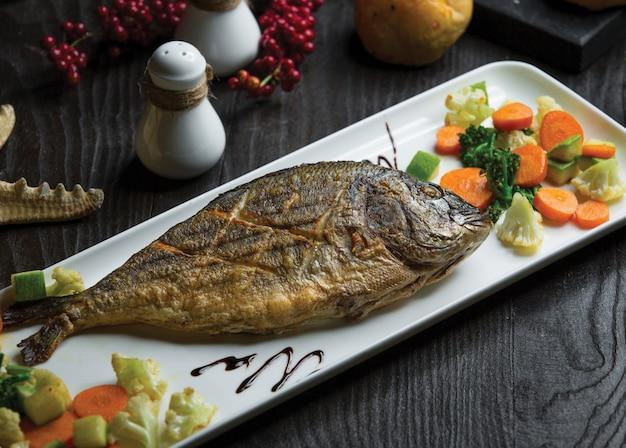 Pesce intero alla griglia con insalata di carote di cavolfiore Foto Gratuite