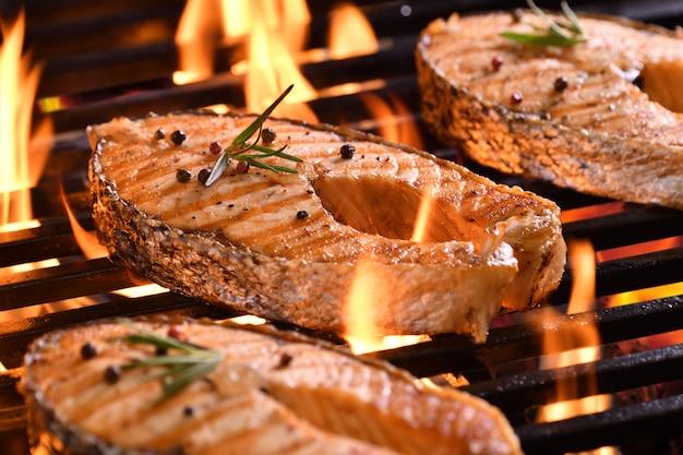 Pesce salmone alla griglia con verdure varie sulla griglia ardente Foto Premium