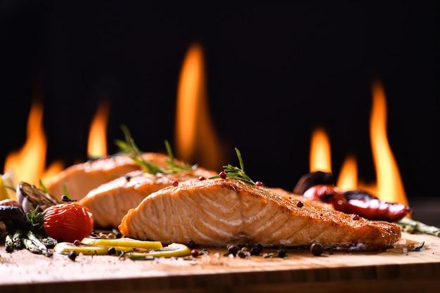 Pesce salmone arrostito e varie verdure sulla tavola di legno Foto Premium