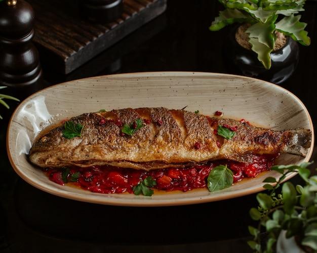Pesce saltato in salsa di melograno e servito in un piatto di granato Foto Gratuite