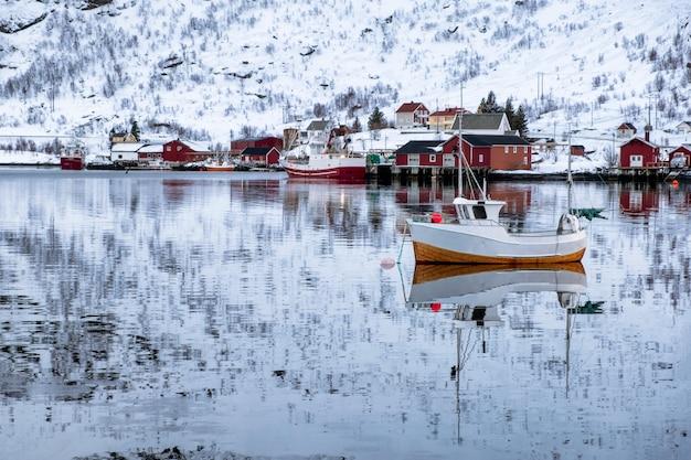 Peschereccio che galleggia e riflessione sulla spiaggia nel villaggio scandinavo Foto Premium