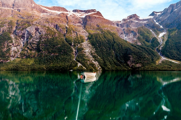 Peschereccio su un lago tranquillo con alte montagne sullo sfondo Foto Gratuite