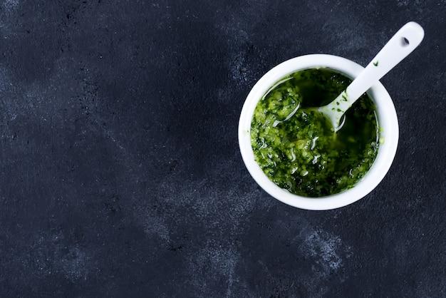 Pesto casalingo del basilico con prezzemolo in ciotola. Foto Premium