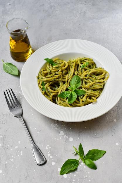 Pesto di spaghetti di pasta con basilico fresco e olio d'oliva Foto Premium