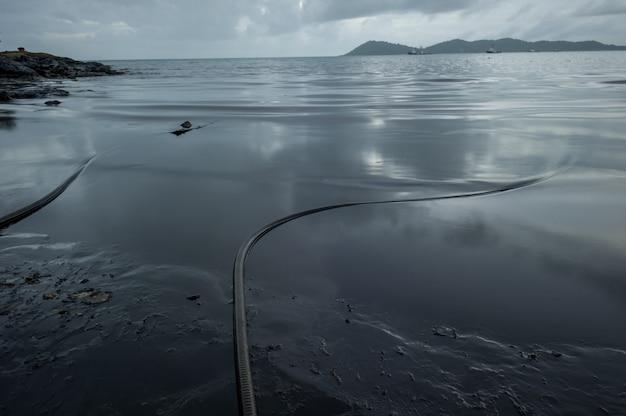 Petrolio greggio lungo la spiaggia di ao phrao dopo una fuoriuscita di petrolio nelle vicinanze nel golfo di thailandia. Foto Premium
