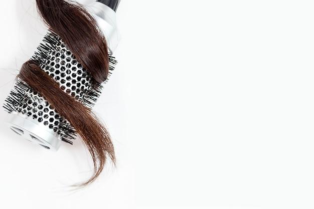 Pettine con capelli scuri isolato su sfondo bianco vista dall'alto Foto Premium