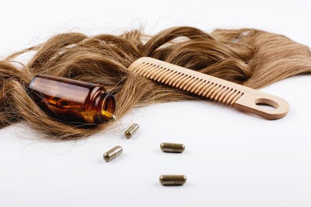 Pettine per capelli in legno e bottiglia con vitamine si trovano su riccioli di capelli castani Foto Gratuite