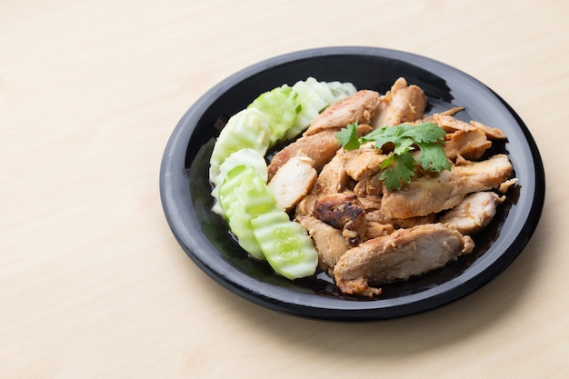 Petto di pollo arrostito parzialmente affettato con il cetriolo in banda nera sulla tavola di legno. Foto Premium