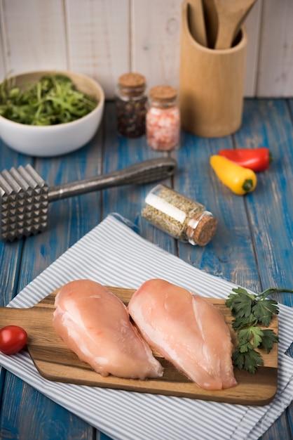 Petto di pollo dell'angolo alto sul bordo di legno con prezzemolo Foto Gratuite