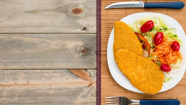 Petto di pollo fritto e insalata di insalata di cavoli in lamiera sul tavolo di legno Foto Gratuite
