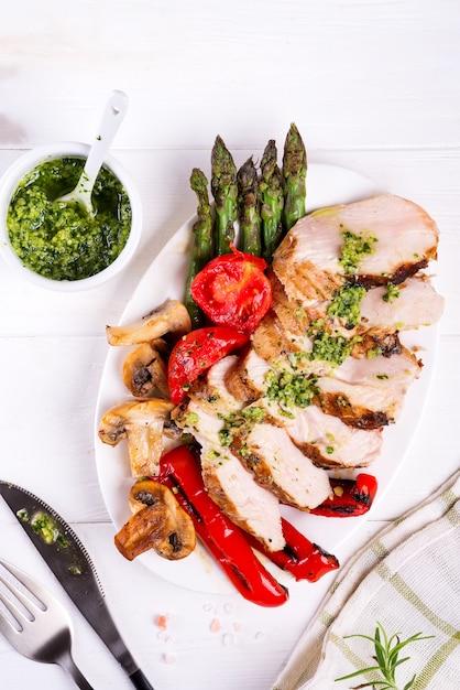 Petto di pollo grigliato su un piatto con pomodori, asparagi e funghi su un piatto, piatto disteso Foto Premium