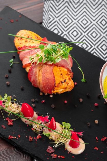 Petto di pollo ripieno avvolto in pancetta su un primo piano piatto Foto Premium