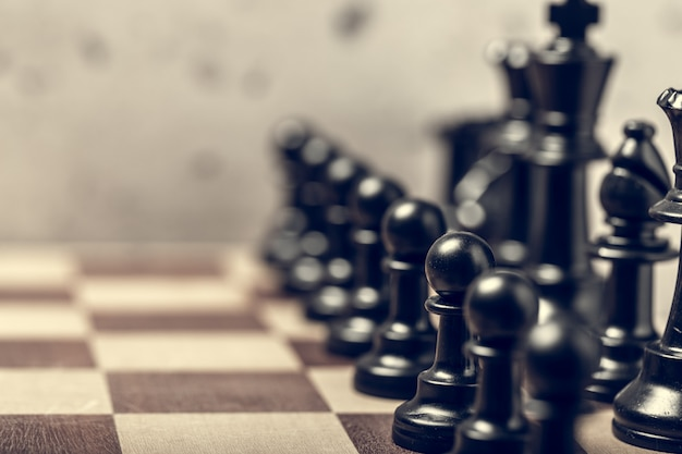 Pezzi degli scacchi sul bordo nel fuoco selettivo della sfuocatura Foto Premium