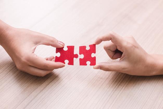 Pezzi del puzzle della tenuta della mano della donna in ufficio Foto Premium
