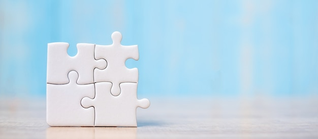 Pezzi del puzzle sul tavolo di legno. soluzioni, obiettivo della missione Foto Premium