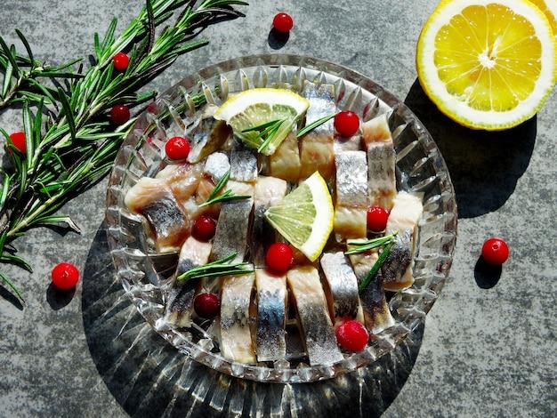 Pezzi di aringhe in un piatto di cristallo. mirtillo, limone e rosmarino. aringhe norvegesi Foto Premium