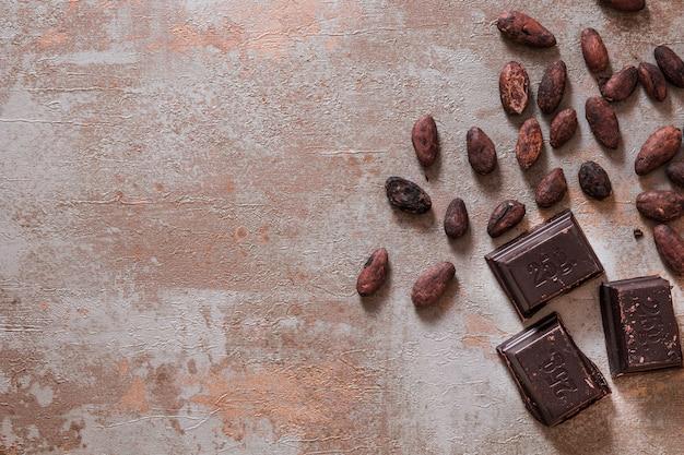 Pezzi di cioccolato con fave di cacao crude su fondo rustico Foto Gratuite