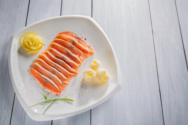 Pezzi di filetto di salmone crudo servito con spezie, limone, burro ed erbe sul piatto bianco e tavolo in legno Foto Premium