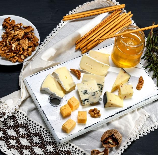 Pezzi di formaggio diverso sul bordo di legno bianco vicino a un barattolo con miele Foto Premium