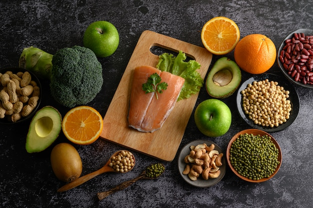 Pezzi di legumi, frutta e pesce salmone su un tagliere di legno. Foto Gratuite