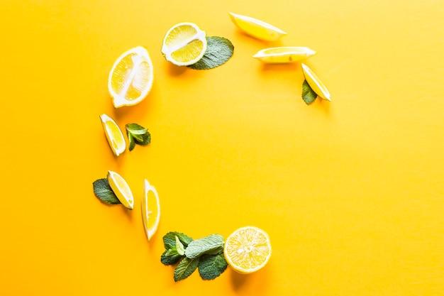 Pezzi di limone, lime e foglie di menta verde allineati in un cerchio Foto Premium
