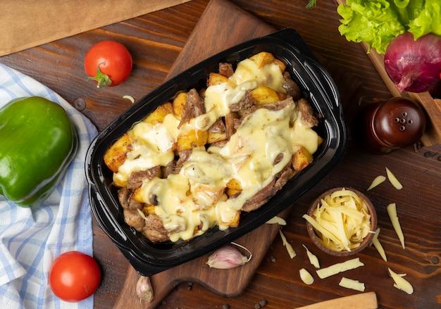 Pezzi di manzo arrostito alla griglia e fette di patate in crema di formaggio fuso Foto Gratuite