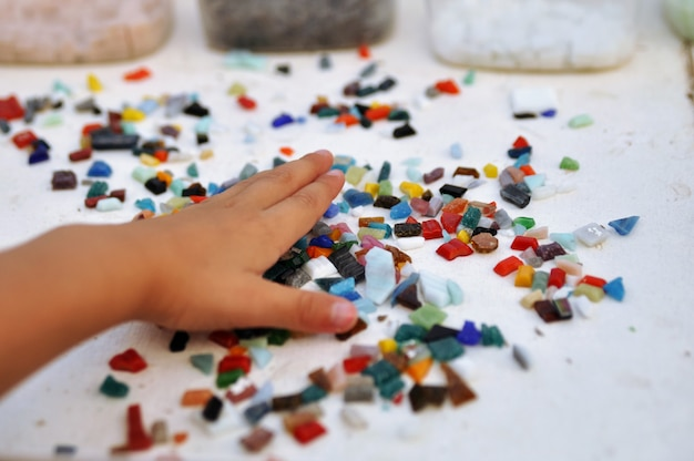 Pezzi di mosaico di vetro colorato nella mano del bambino sul tavolo Foto Premium