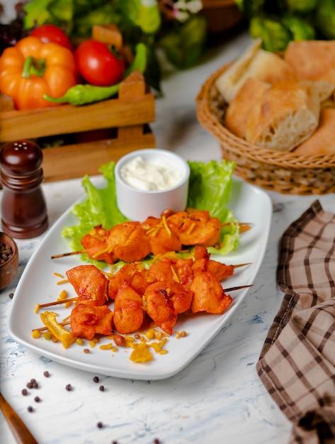 Pezzi di petto di pollo sash kebab, grigliati e serviti con salsa di panna, sumakh e lattuga Foto Gratuite