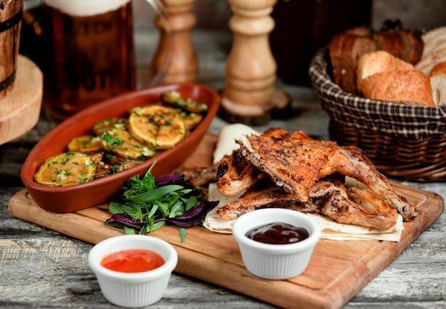 Pezzi di pollo alla griglia serviti con fette di patate arrosto e salse Foto Gratuite
