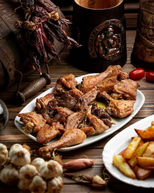 Pezzi di pollo grigliati e server con patatine fritte. Foto Gratuite