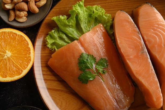 Pezzi di salmone su un piatto di legno. messa a fuoco selettiva. Foto Gratuite