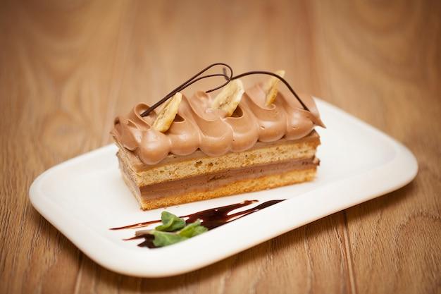 Pezzo di dolce di cioccolato saporito sul fondo di legno della tavola Foto Premium