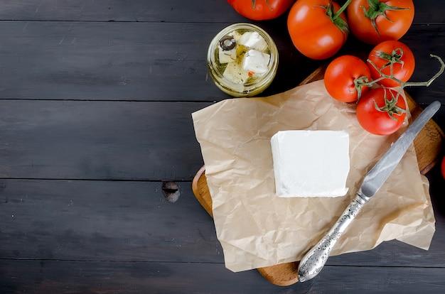 Pezzo di formaggio a pasta molle sulla tavola e feta piccante marinata in un barattolo e pomodori per insalata. Foto Premium