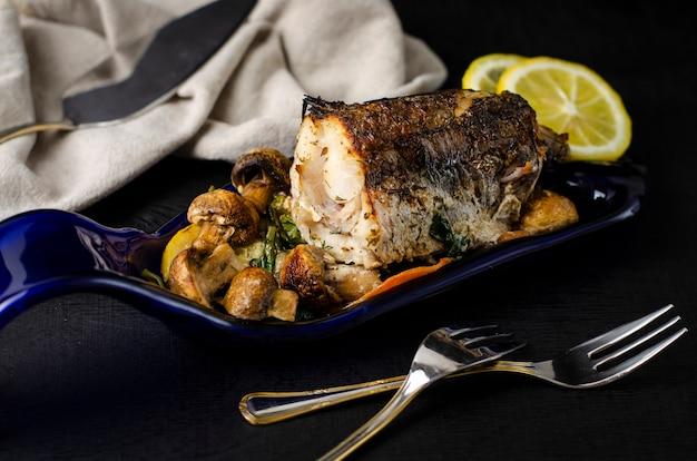 Pezzo di pesce al nasello al forno con verdure su un piatto blu fatto dalla bottiglia Foto Premium