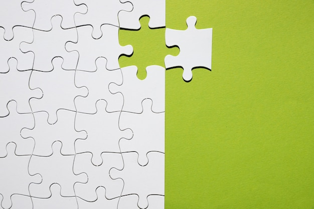 Pezzo di puzzle bianco separato con griglia di puzzle bianca su sfondo verde Foto Gratuite