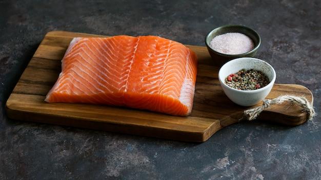 Pezzo di salmone fresco crudo sul tagliere Foto Premium