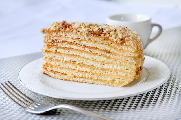 Pezzo di torta a strati con crema pasticcera e noci su un piatto Foto Premium