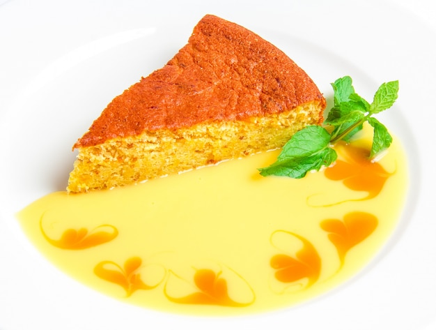 Pezzo di torta con salsa gialla Foto Gratuite