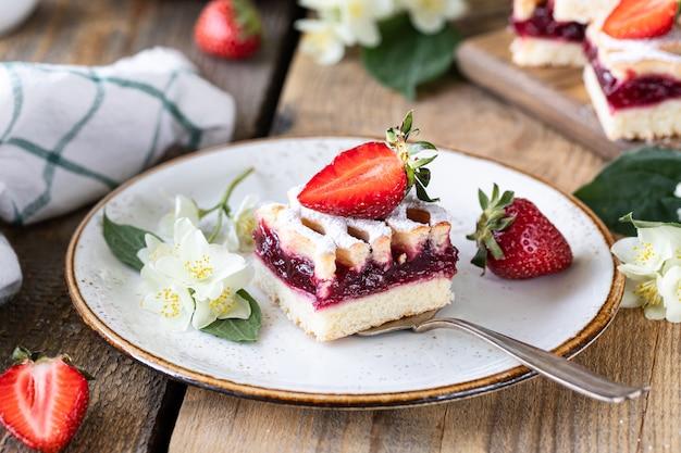 Pezzo di torta saporita con le fragole su un piatto bianco sulla tavola di ooden. Foto Premium