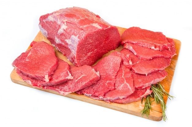 Pezzo enorme di carne rossa e bistecca sul tavolo di legno Foto Premium