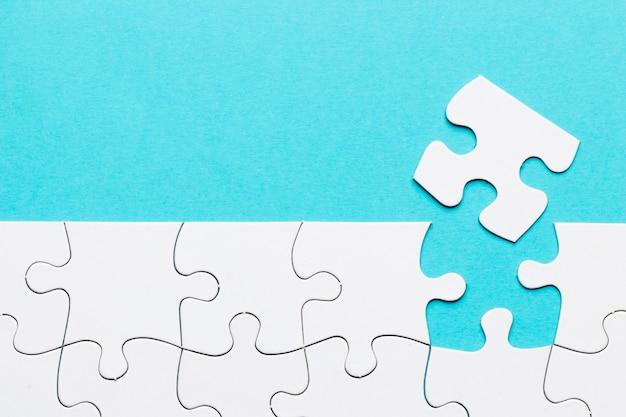 Pezzo mancante di puzzle con la griglia bianca di puzzle su fondo blu Foto Gratuite