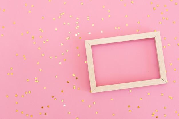 Photo frame mock up con spazio per il testo, coriandoli oro paillettes su sfondo rosa. Foto Premium