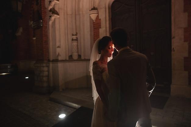 Photosession notturno degli sposi a cracovia, gli sposi camminano intorno alla chiesa Foto Premium
