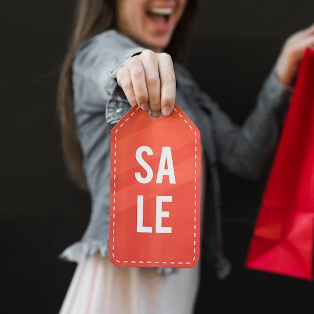 Piangere donna con il pacchetto dello shopping e segno di vendita Foto Gratuite