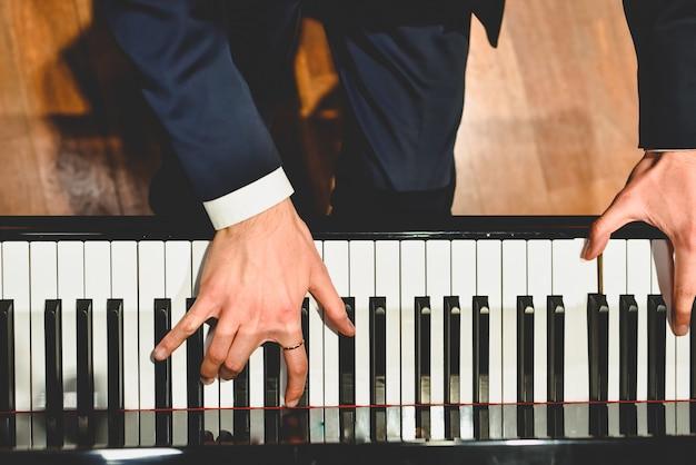 Pianista esegue un brano su un pianoforte a coda con tasti bianchi e neri Foto Premium
