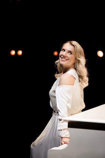 Pianista in posa vicino al pianoforte bianco sul palco Foto Premium