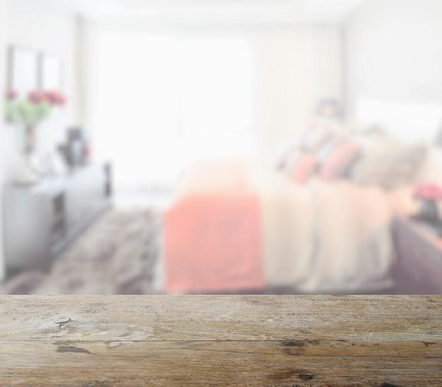 Piano d'appoggio di legno con la sfuocatura dell'interno moderno della camera da letto come fondo Foto Premium