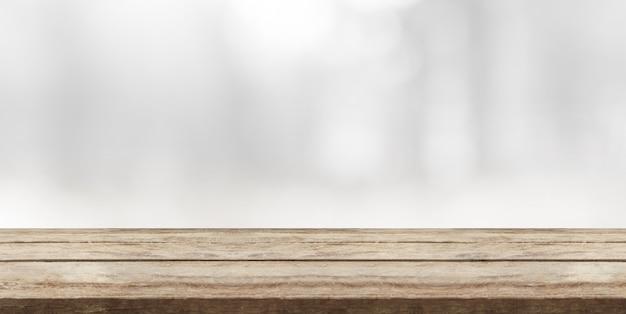 Piano d'appoggio di legno davanti allo spazio bianco astratto del fondo e della copia del bokeh. Foto Premium